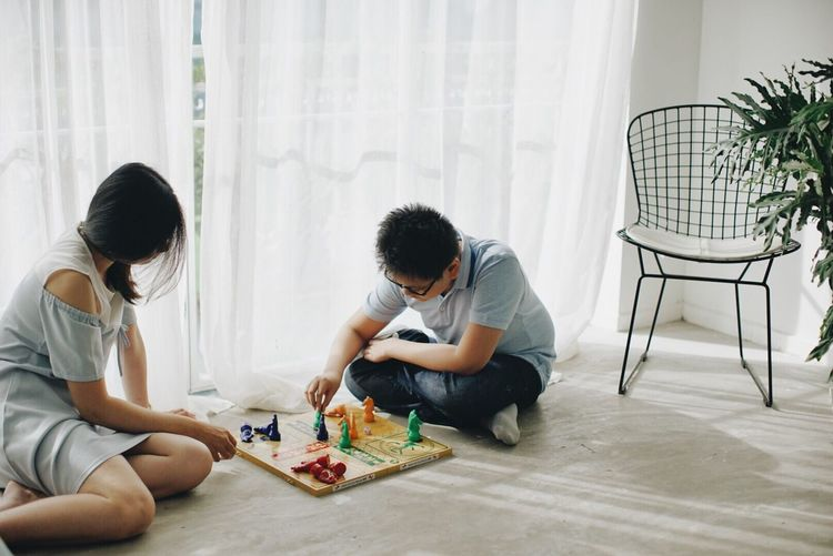 Rear view of two people sitting on table