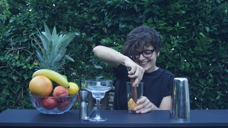 Smiling young woman preparing juice against plants