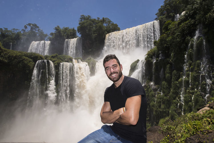 Portrait of young man against waterfall