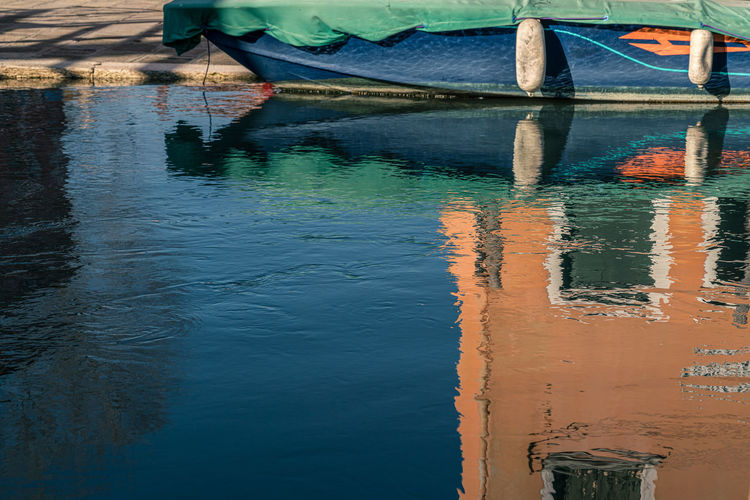 Boat moored in canal with reflections on water