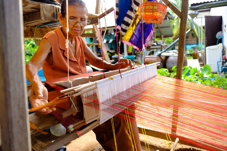 Close-Up Of Senior Woman Weaving On Equipment