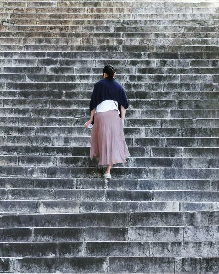 Rear view of woman standing on staircase against brick wall