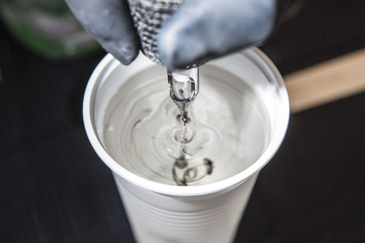 Close-Up Of Woman Pouring Water Into Cup