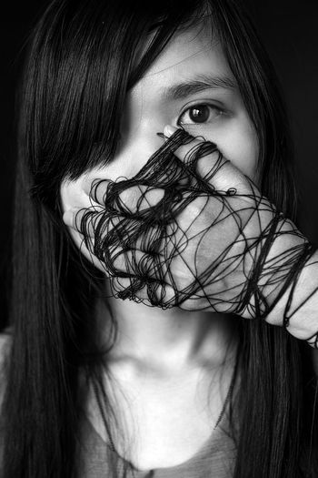 Close-up portrait of young woman wrapped with hair