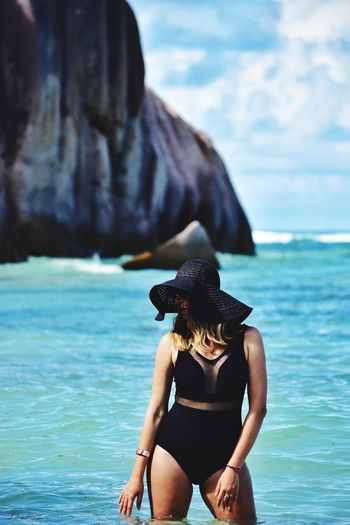 woman in black summer hat and swimsuit on anse source d'argent on la digue island in Seychelles Swimsuit Swimwear Hat Seychelles La Digue Girl Woman Holiday Ocean Indian Ocean Vacation Holiday Travel Water Sea Beach Adventure Swimming Bikini One Piece Swimsuit
