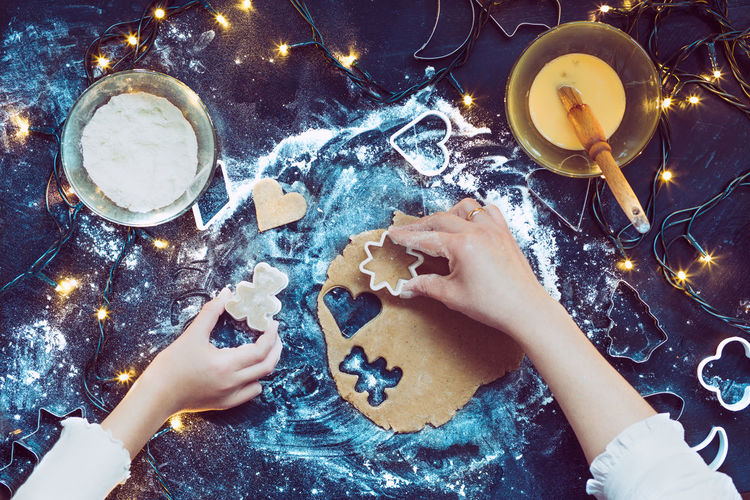 High angle view of hands making christmas cookies