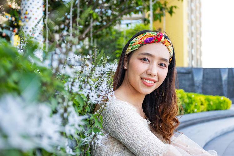 Portrait of young woman wearing headwear sitting against plants
