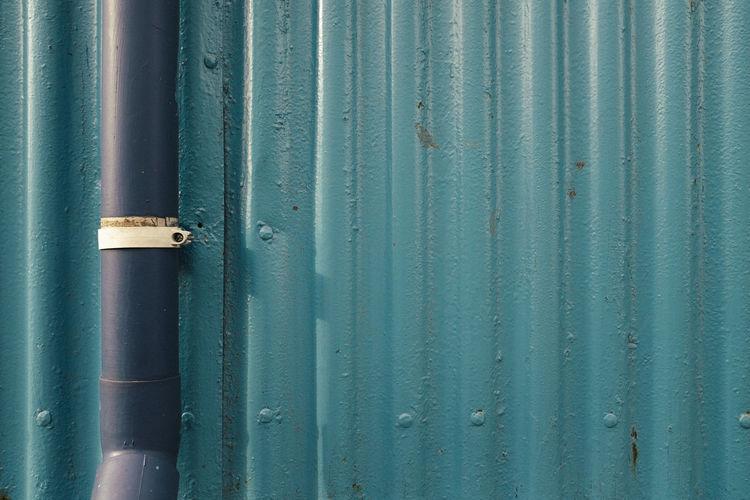 Pipe On Corrugated Iron Fence