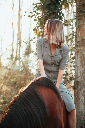 Woman sitting on horse in forest