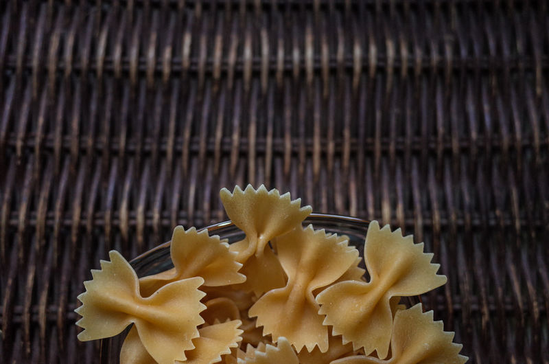 High angle view of raw farfalle pasta on wicker