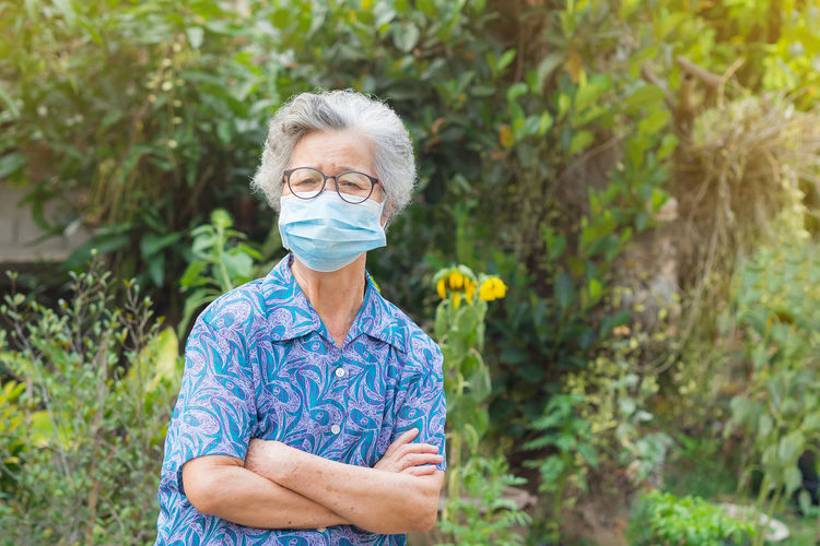 A portrait of an elderly woman wearing a face mask and arms crossed while standing in a garden.