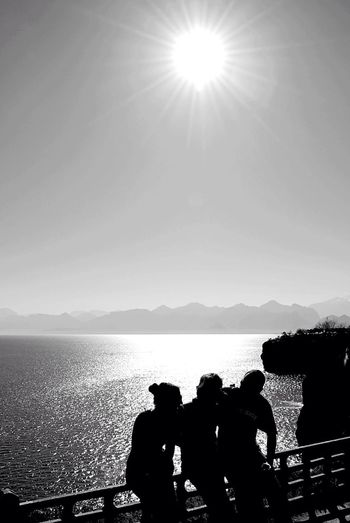 Silhouette people photographing sea against clear sky