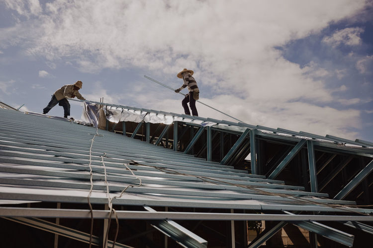 Low angle view of men working on rooftop against sky