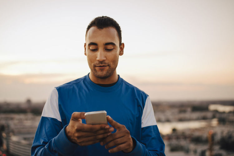 Portrait of young man using mobile phone against sky