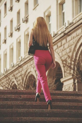 Rear view of woman walking on staircase in building