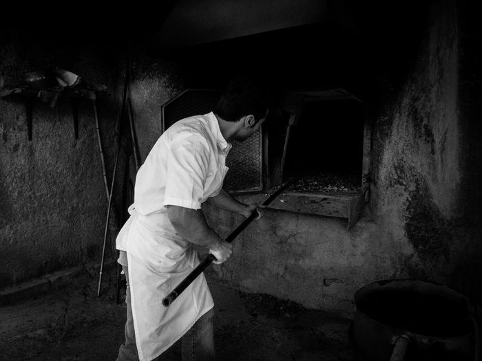 Side view of man working at bakery