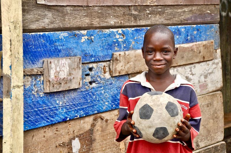 Portrait Of Teenage Boy Smiling While Holding Soccer Ball Against Wall