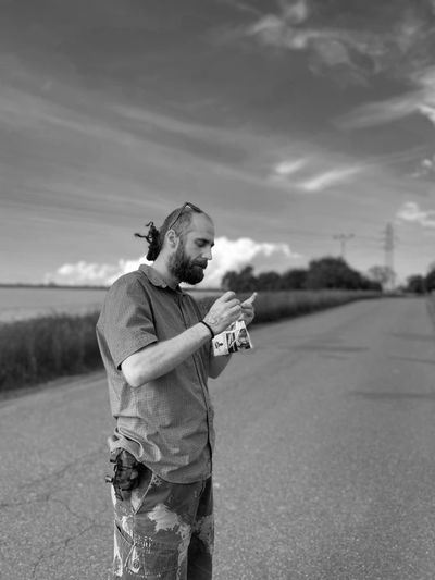 Man holding umbrella standing on road against sky