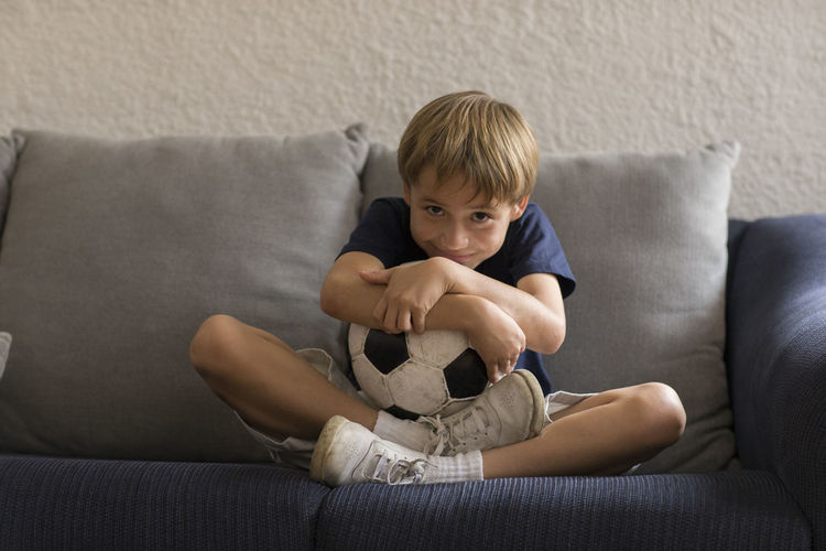 Portrait Of Boy With Soccer Ball Sitting On Sofa At Home