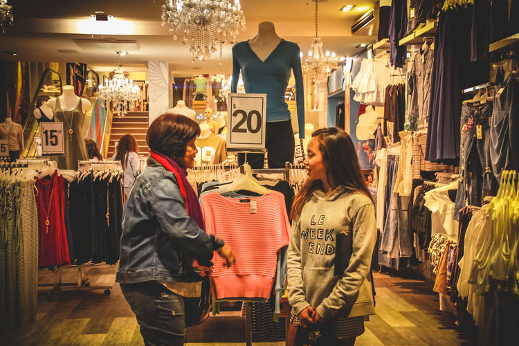 Arts Culture And Entertainment Boutique Buying Casual Clothing Choice Clothing Clothing Store Consumerism Customer  Day Fashion Indoors  Leisure Activity Lifestyles People Real People Retail  Small Business Standing Store Togetherness Two People Women Young Adult Young Women This Is Family