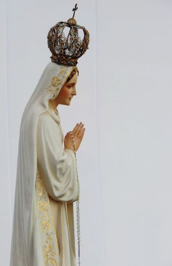 Virgin Mary Statue Against White Wall