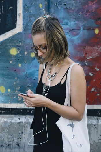 Woman using mobile phone while standing against wall with graffiti