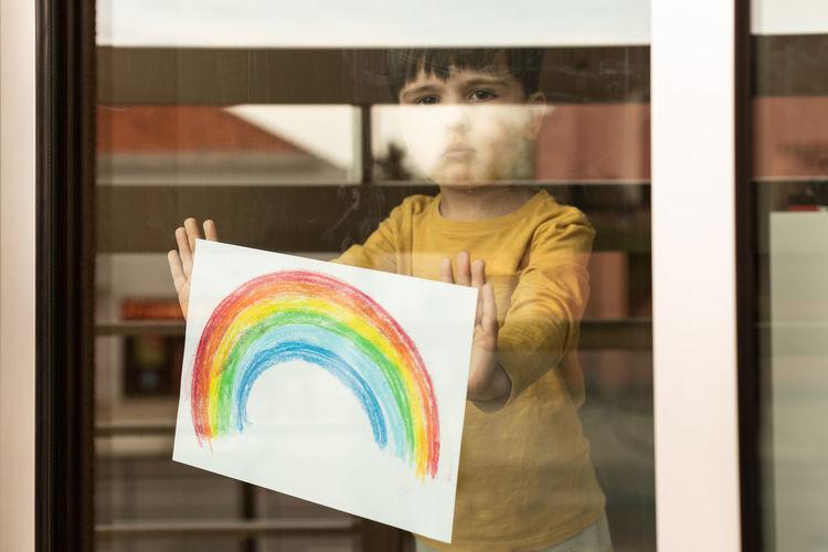 Portrait of boy holding multi colored rainbow painting seen through window