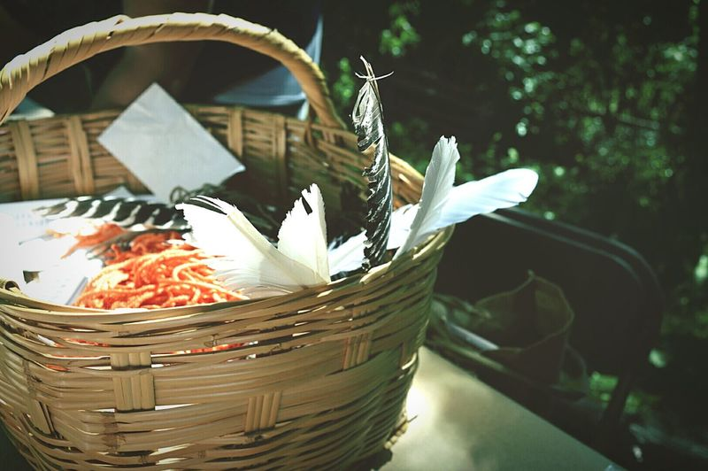 Feathers In Wicker Basket On Table