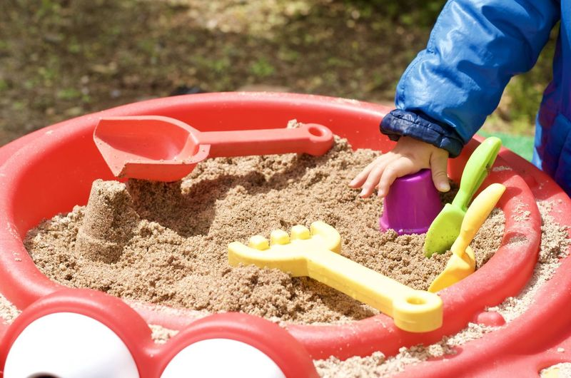 High angle view of child playing with toy on sand