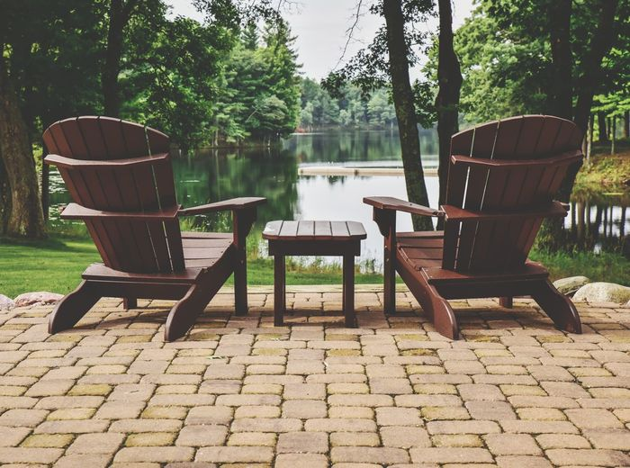 Empty Adirondack chairs overlooking lake in summer Tree Chair Lake Water Furniture Outdoor Chair Outdoors No People Day Nature Seat Beauty In Nature Sky Green Color Bradley Olson Bradleywarren Photography Adirondack Chairs Patio Furniture Brick Patio Lake View Scenics Landscape Room For Text Room For Copy Copy Space Lost In The Landscape