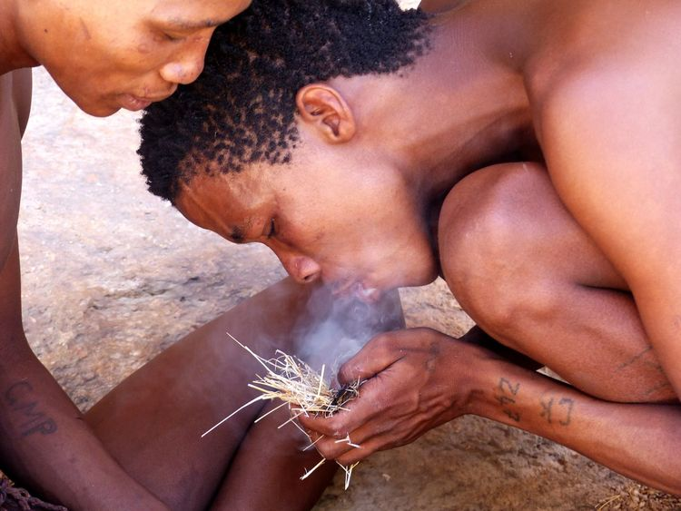 Two members of the traditional San-tribe show how to start a fire. Close-up Survival Traditional Shirtless Tattoo Way Of Living Traditional Culture Africa Erongo Fire Firemaking Smoke Fume Handwork San Tribe Natives Native