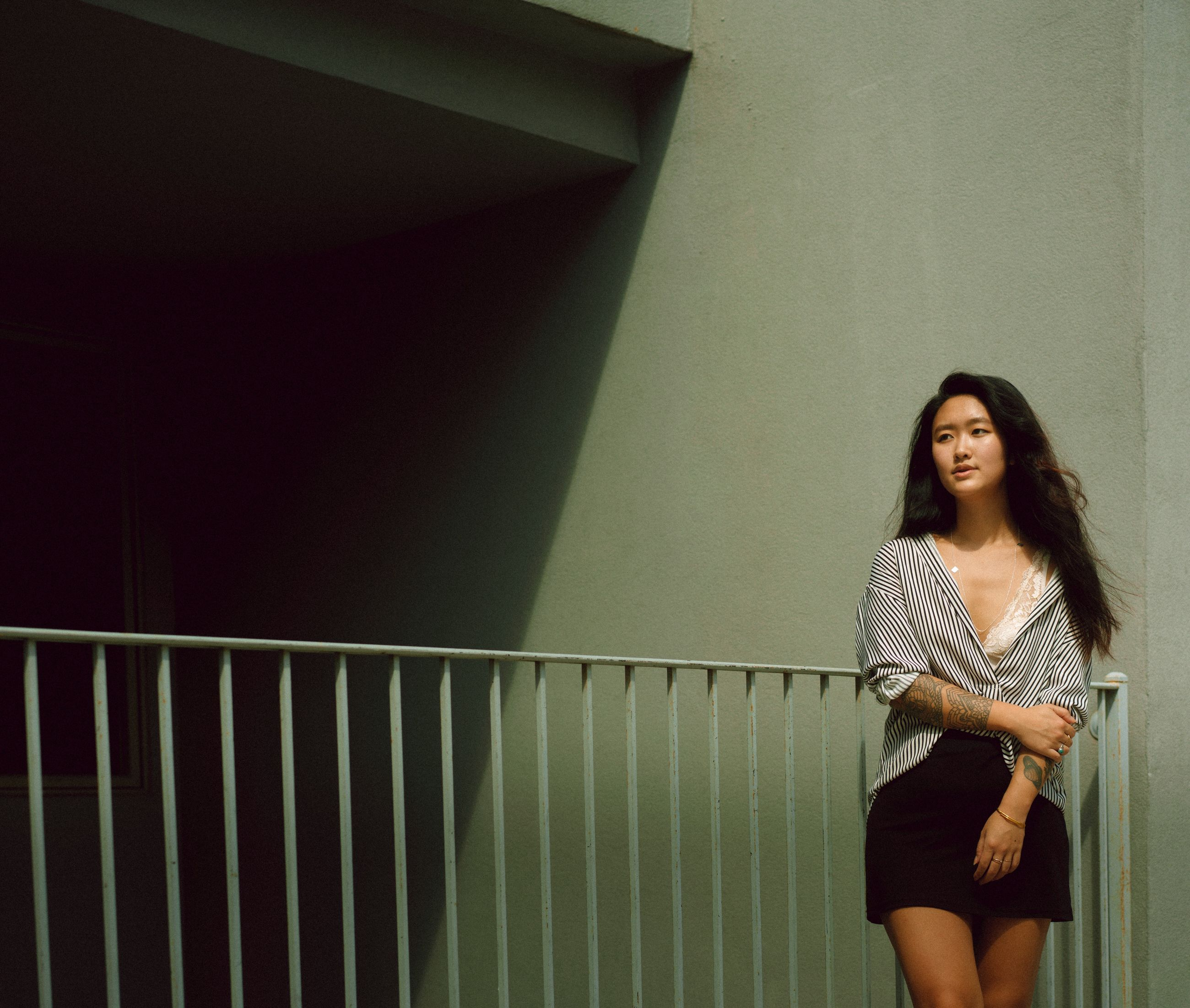 one person, real people, three quarter length, standing, young women, casual clothing, young adult, lifestyles, railing, smiling, women, leisure activity, front view, portrait, wall - building feature, looking at camera, architecture, indoors, long hair, beautiful woman, hair, hairstyle, contemplation