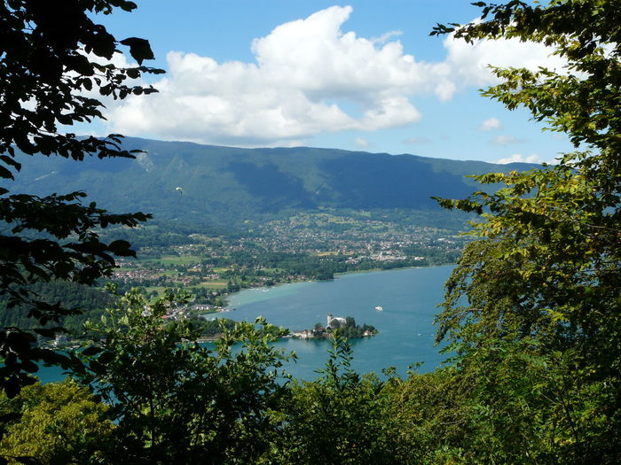 Scenic view of mountains and lake annecy seen through trees