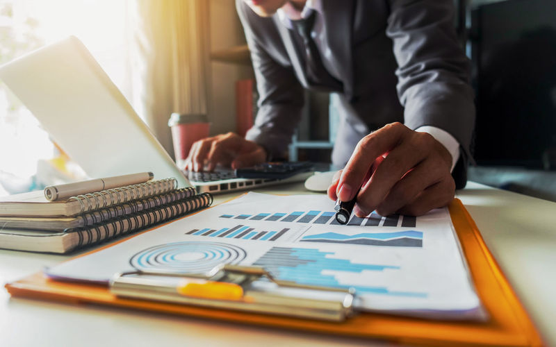 Midsection of businessman pointing on graph while using laptop on table