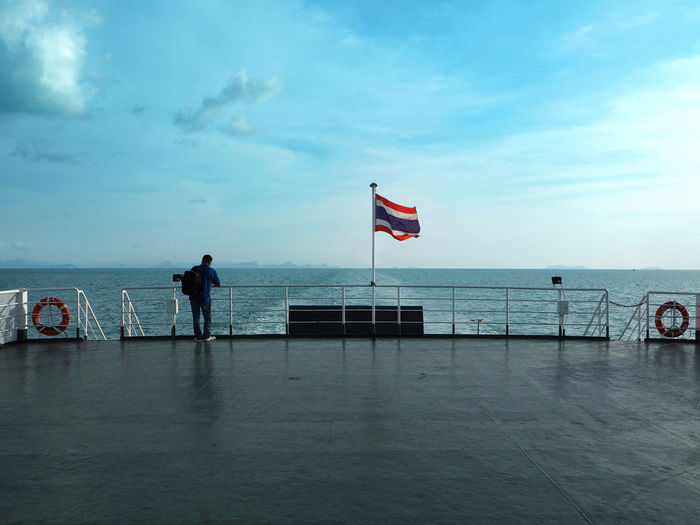 Rear view of man standing in front of thai flag waving on boat sailing in sea
