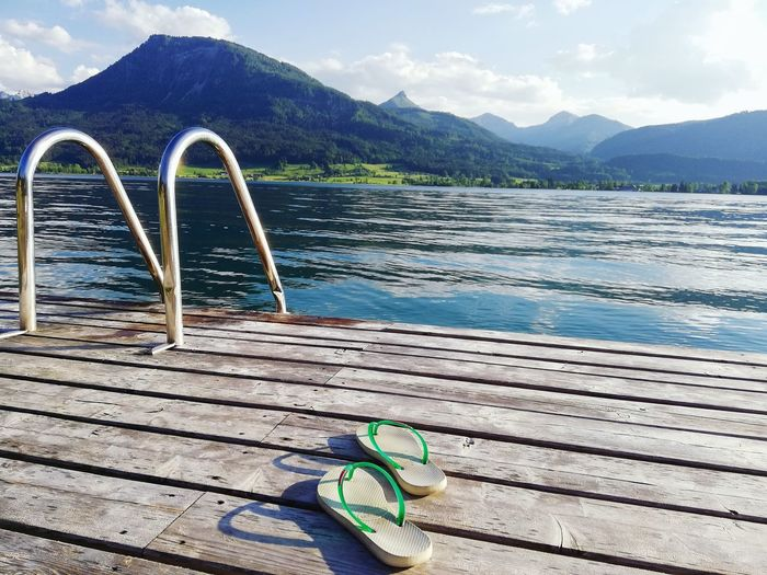 Slippers on pier over lake against mountains