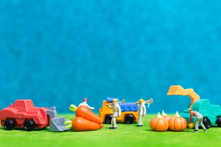 Close-up of toys and figurine on green table