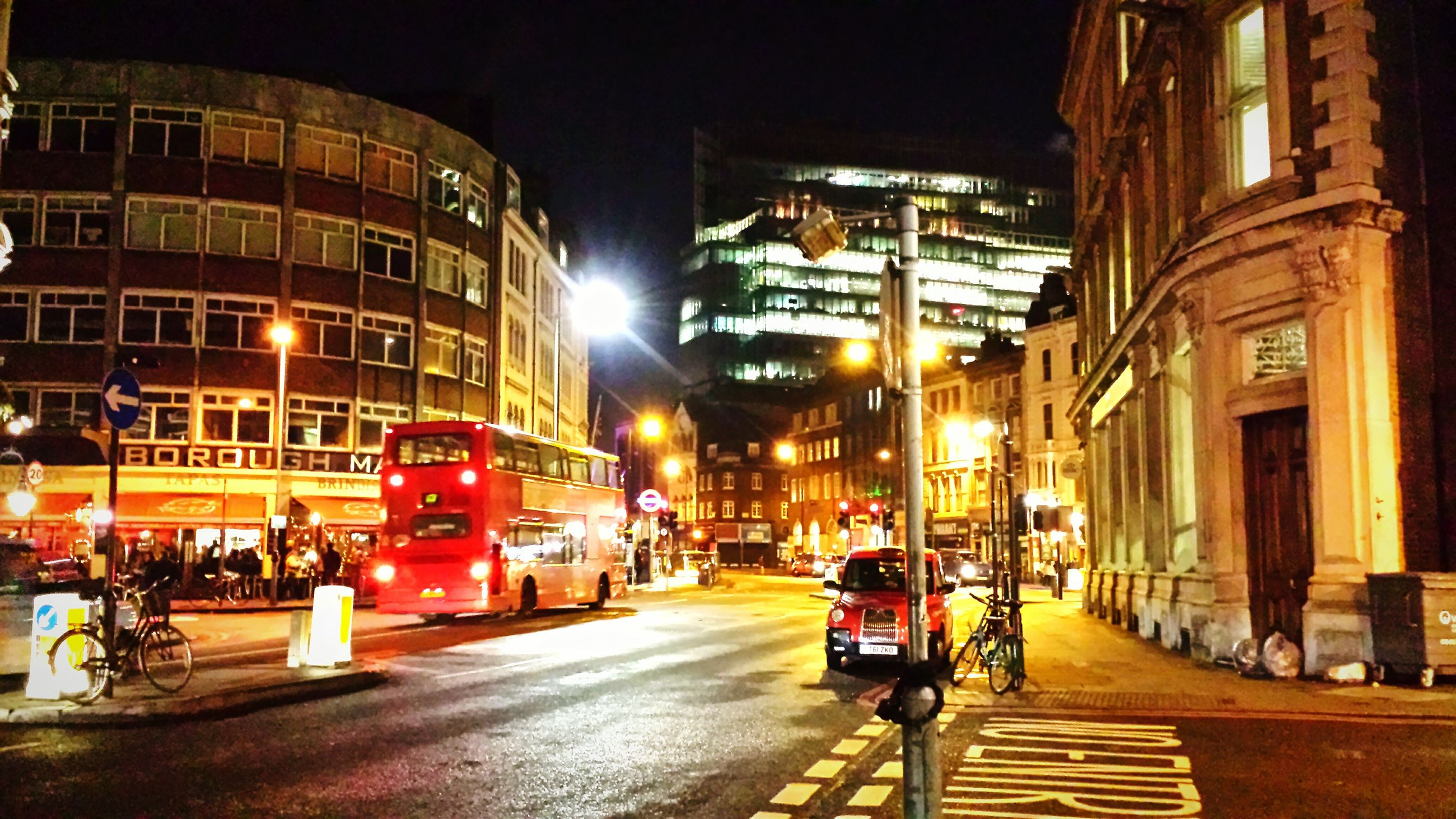 building exterior, architecture, built structure, city, illuminated, street, transportation, night, car, land vehicle, city life, mode of transport, city street, road, incidental people, the way forward, building, street light, men