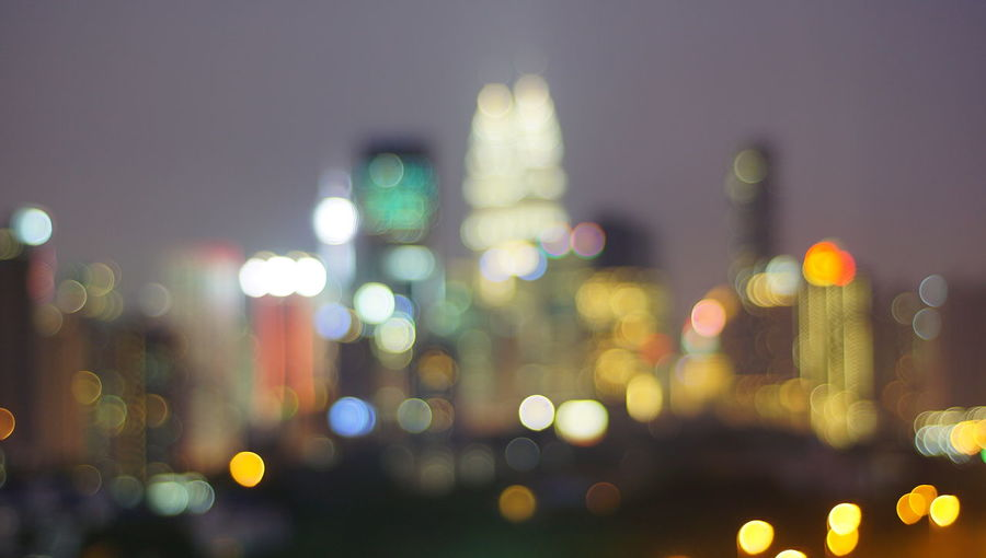 Malaysia city skyline illuminated at night.Blurry photo light and bokeh. Architecture Building Exterior Built Structure Circle City Cityscape Defocused Geometric Shape Glowing Illuminated Lens Flare Light Lighting Equipment Multi Colored Night No People Office Building Exterior Outdoors Shape Sky Skyscraper Street Transportation Vehicle Light