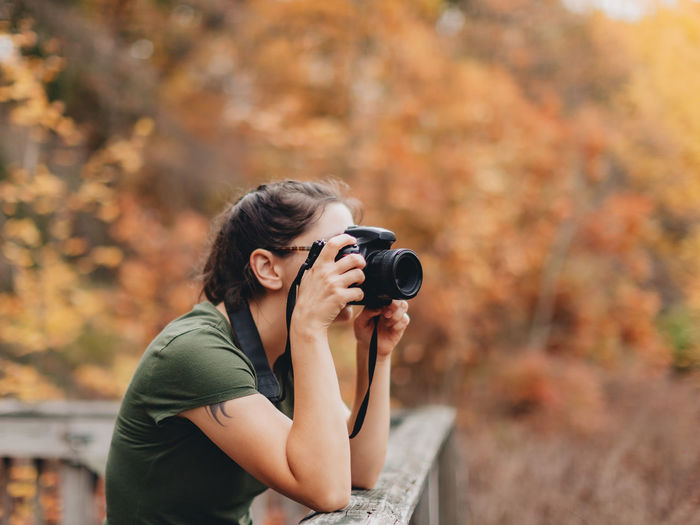 Young woman photographing during autumn