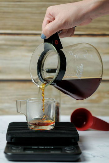 Cropped image of person pouring coffee in glass