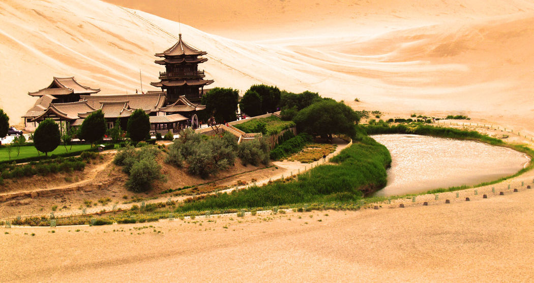 This is China Chinese Architecture Desert Green Oasis Park Sand Island Architecture Arid Climate Building Exterior Built Structure Desert Landscape Oasis Outdoors Sand Sand Dune Small Island Temple - Building Tree Water Spring Yellow Yellow Color