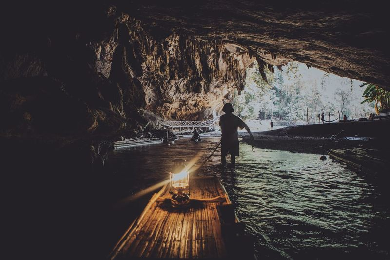Rear View Of Man Pulling Wooden Raft With Lantern In Cave