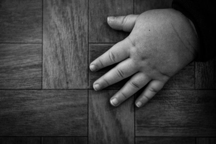 Close-up of baby hand on wooden floor