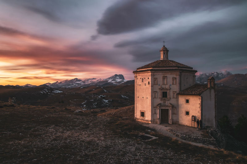 Old chapel on mountain against cloudy sky during sunset
