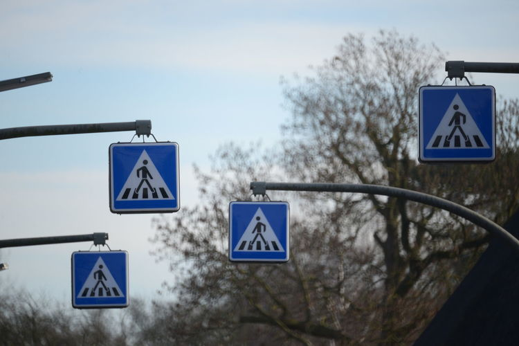 Low Angle View Of Pedestrian Crossing Signs Against Sky