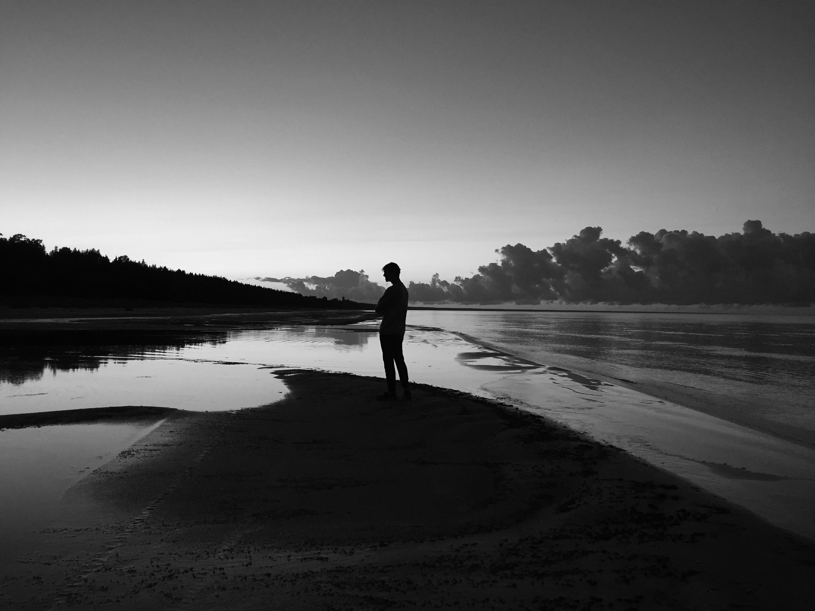 beach, water, full length, tranquility, clear sky, sand, tranquil scene, leisure activity, shore, standing, lifestyles, copy space, rear view, silhouette, scenics, walking, sea, beauty in nature
