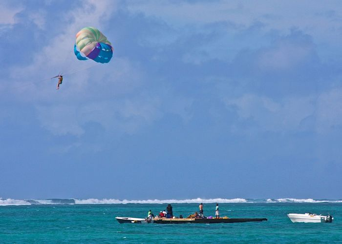 People on floating board with person parasailing against cloudy sky