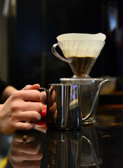 Cropped hands of bartender holding mug on table in cafe