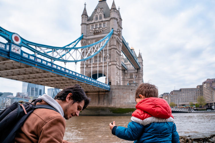 Father and son by thames river in city